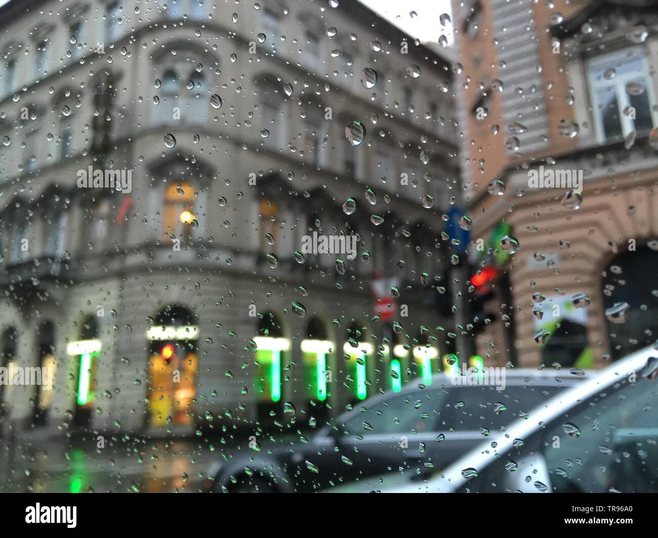 City lights and old architecture of Budapest, Hungary, through the blurred windshield of car with rain drops - Stock Image