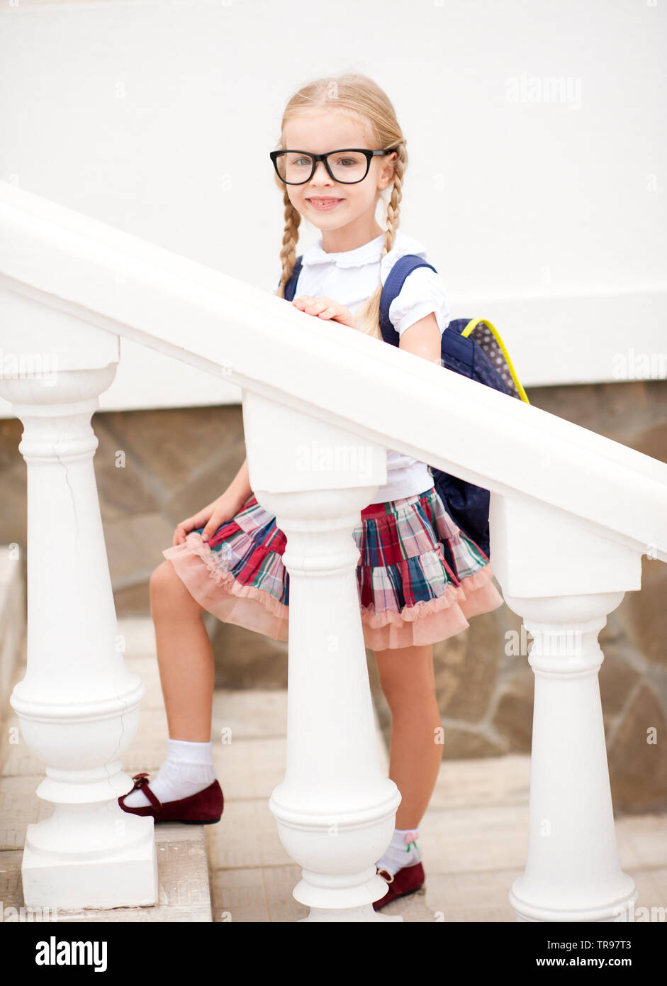 Cute child girl 6-7 year old going upstairs outdoors. Looking at camera. Back to school. Childhood. - Stock Image