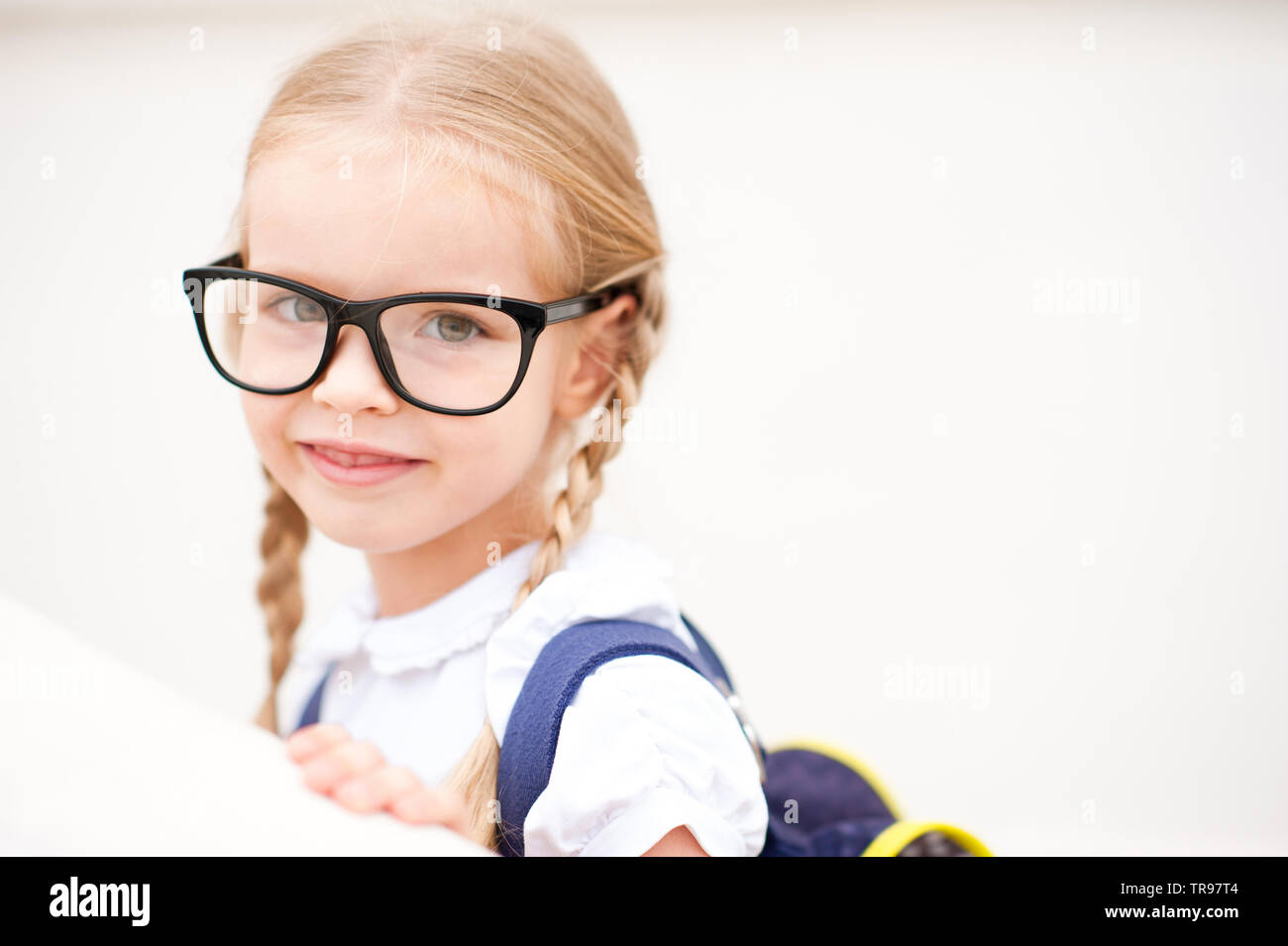 Smiling kid girl 6-7 year old wearing glasses and school bag outdoors. Blonde child looking at camera. Back to school. Childhood. - Stock Image