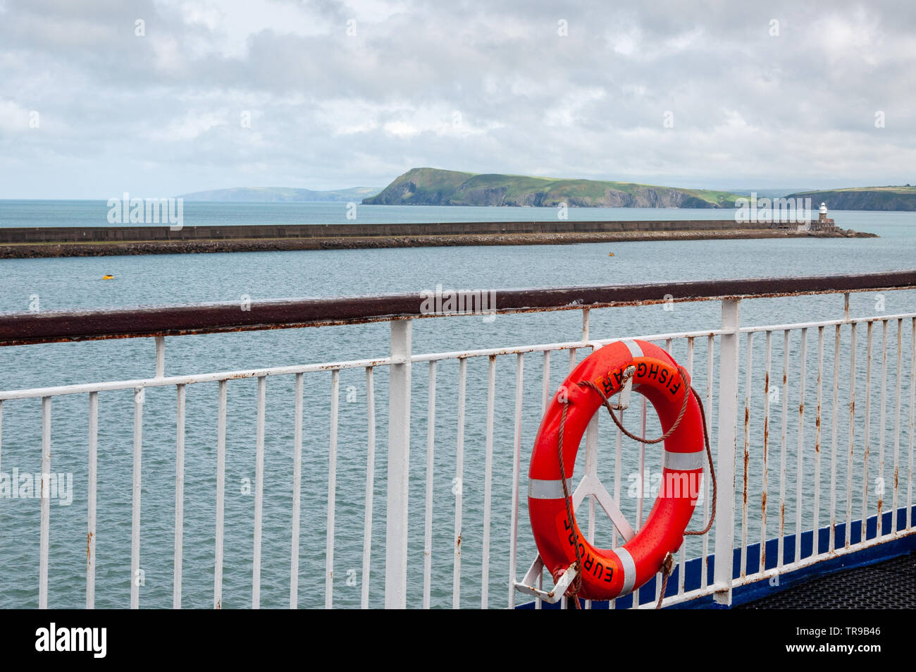 Wales coast. The Fishguard harbour wall and lighthouse as seen from Stena Line ferry deck. Fishguard (Abergwaun), Pembrokeshire,Wales, United Kingdom - Stock Image