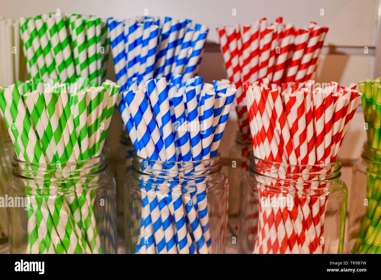 Assorted color striped straws, single use plastic alternative, in jars displayed at booth at National Restaurant Association Show held in Chicago, USA - Stock Image