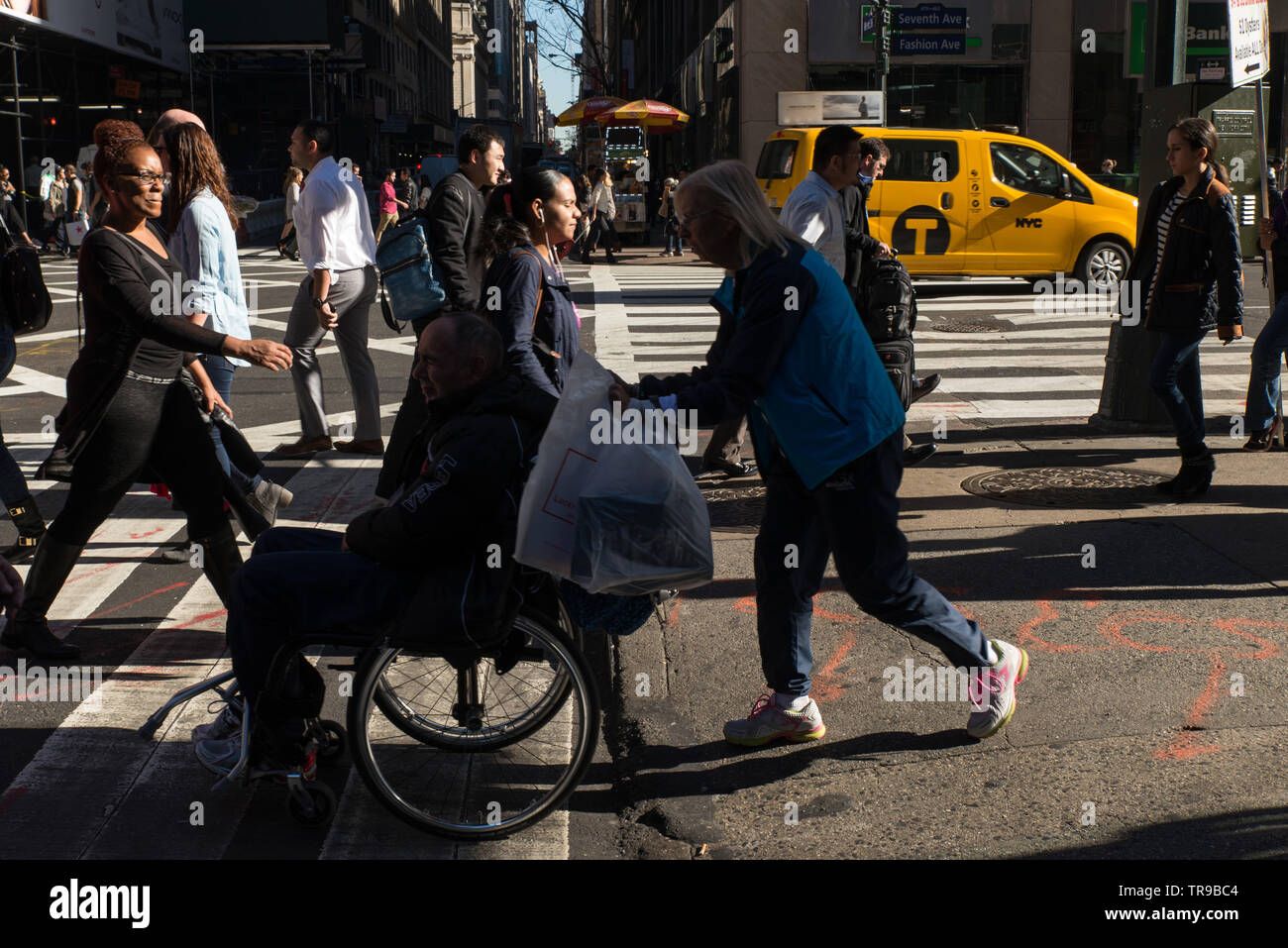 Eine behinderte Person überquert die Straße in einem Rollstuhl, der von einem Begleiter geschoben wird. // A handicapped person crosses the street in Stock Photo