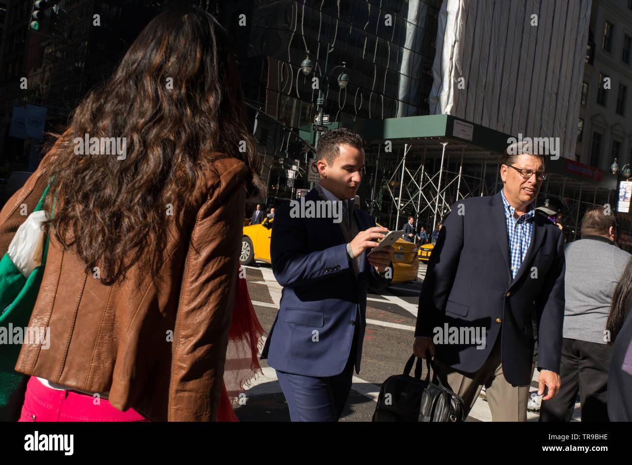 Texting while crossing the street might soon become illegal in NYC // SMS-Nachrichten beim Überqueren der Straße könnten in NYC bald illegal werden. Stock Photo