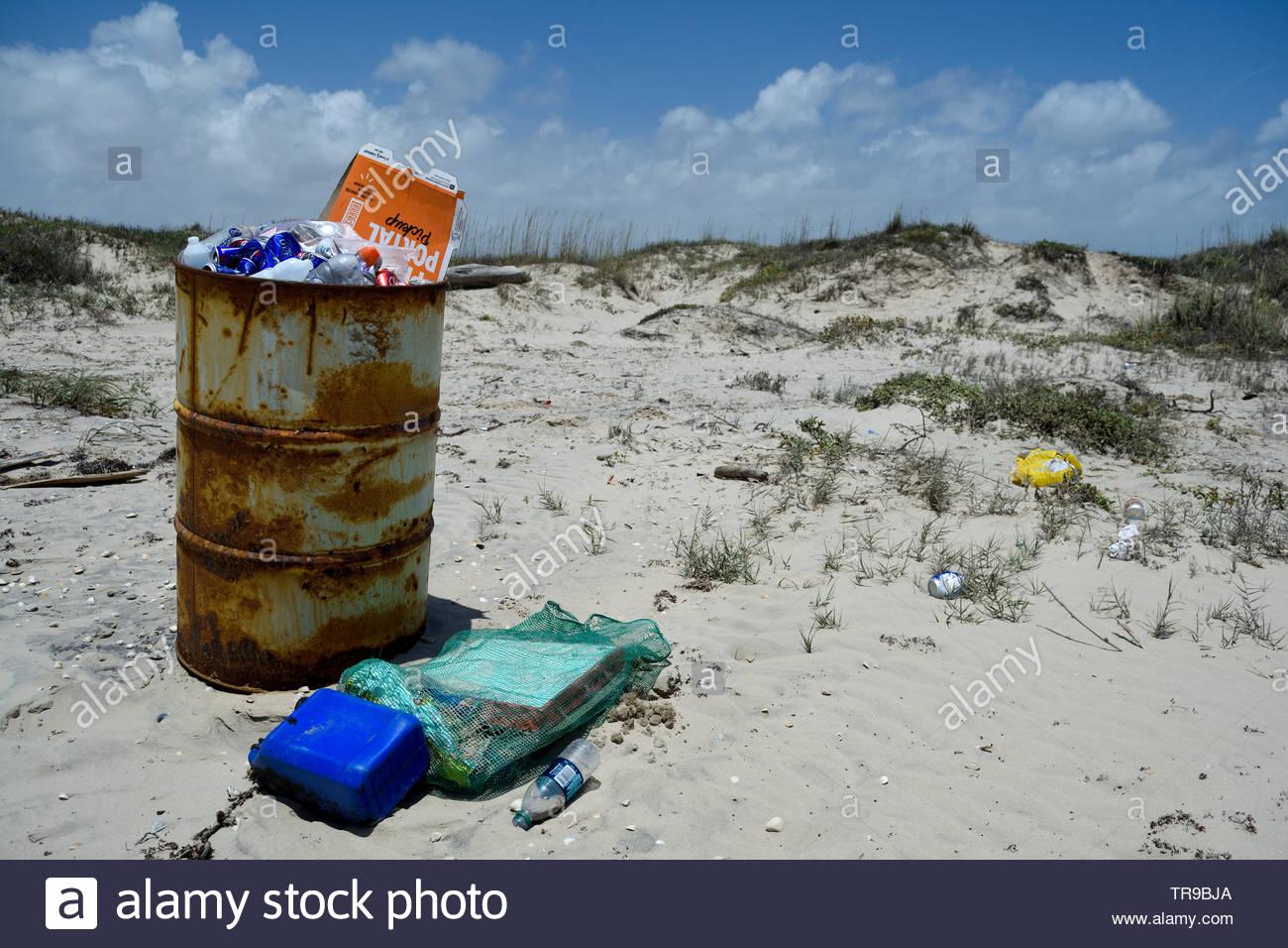 Trash on beach. Overflowing trash can on beach. Trash Barrel overflowing. Garbage Can. Garbage on Texas Beach. Trash left on beach Memorial Day. Trash - Stock Image