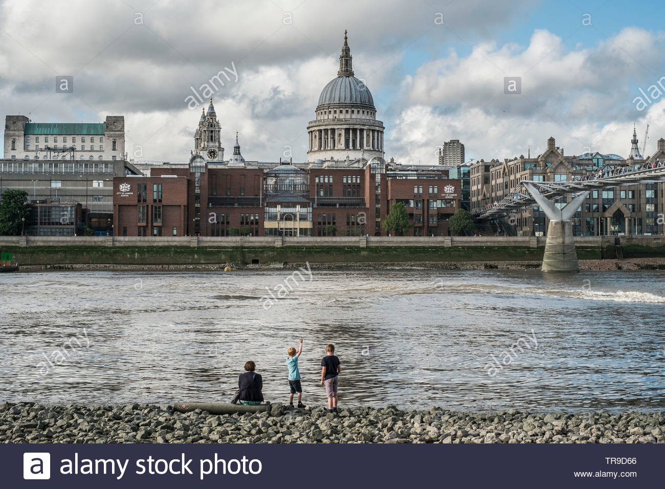 Children playing at low tide on the Thames opposite St Pauls Cathedral London. - Stock Image