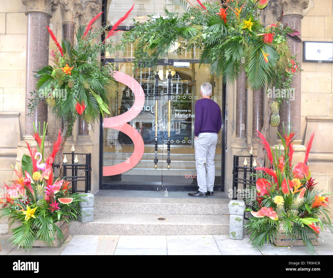 The Manchester Flower Show, part of Manchester's King Street  Festival on June 1st - 2nd, 2019, prepares to open. This year's theme:Flower Power!  A flower display decorates the entrance to an office building on King Sreet. - Stock Image