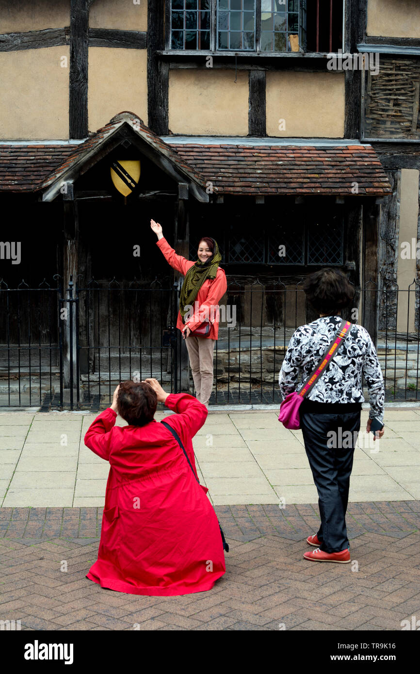 An overseas tourist being photographed outside William Shakespeare`s Birthplace, Stratford-upon-Avon, UK - Stock Image