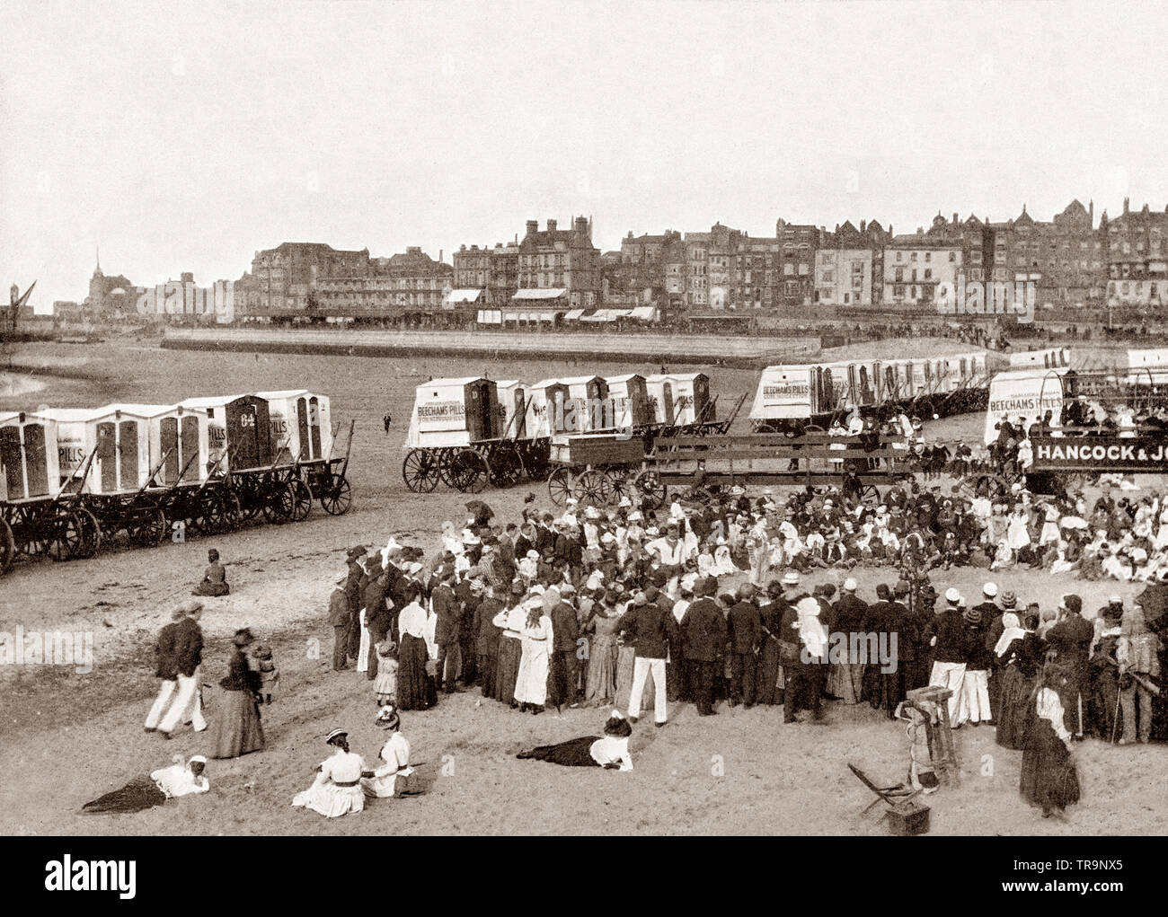 A 19th Century view of beach huts and crowd watching beach entertainment at Margate, a seaside town in Thanet, Kent, South East England. Margate has been a leading seaside resort and a traditional holiday destination for Londoners drawn to its sandy beaches, for at least 250 years. - Stock Image