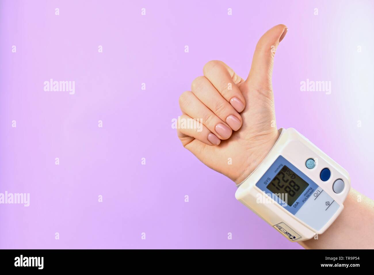 Hand and tonometer, buttoned at the wrist. Diagonally in the center, from the lower right corner. On a purple background. On the scoreboard indicators - Stock Image