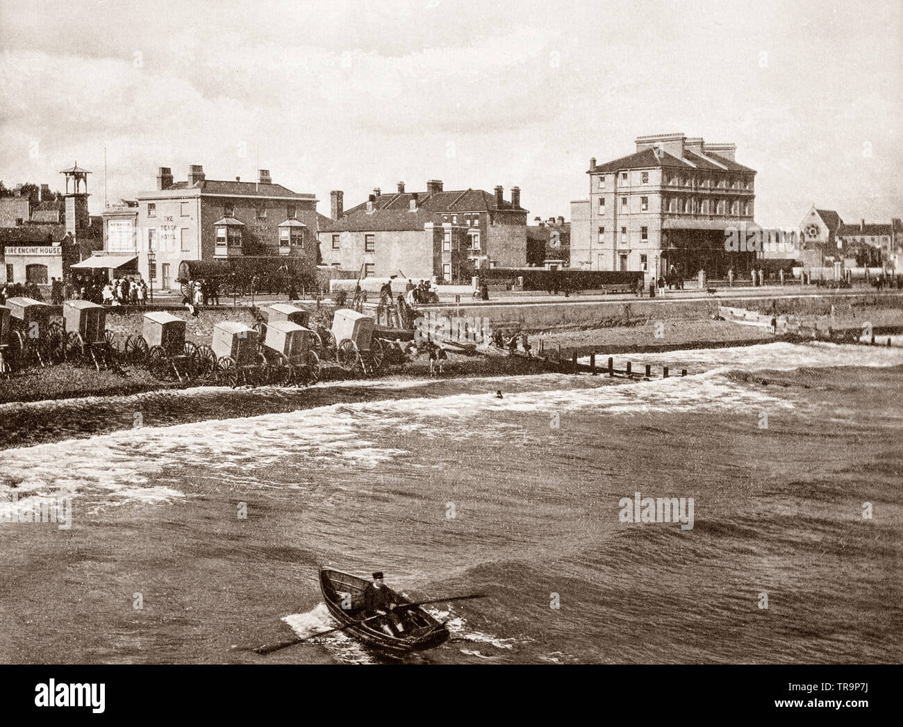 A 19th Century view of bathing huts on Bognor beach. Bognor Regis is a seaside resort in West Sussex on the south coast of England. It was developed slowly in the late 18th century on what was a sandy, undeveloped coastline but grew rapidly following the coming of the railway in 1864. - Stock Image