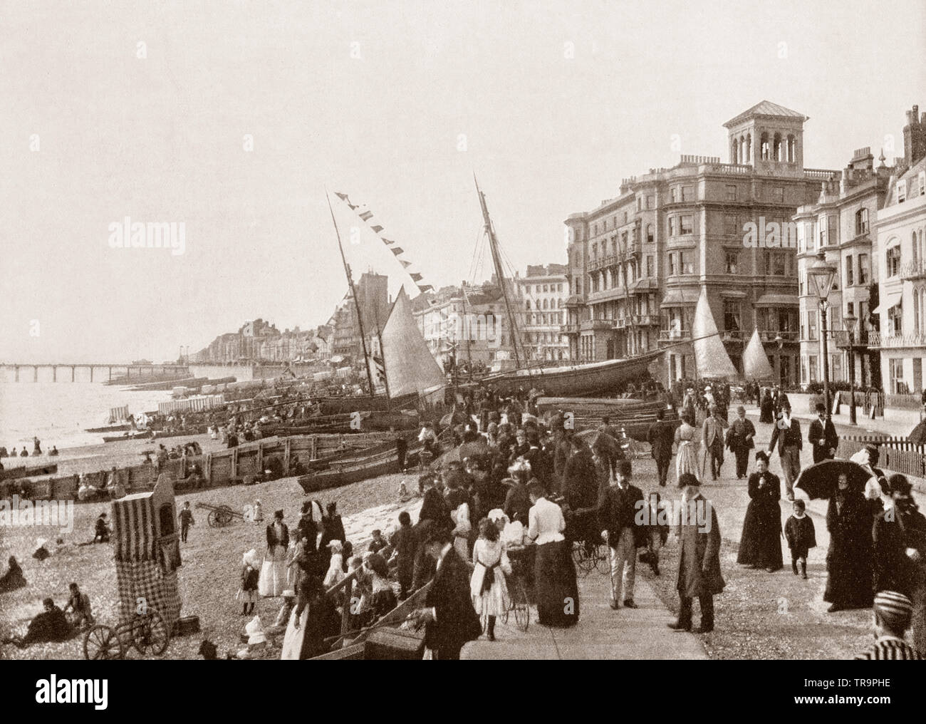 A 19th Century view of  the seafront with yachts in Hastings, a town in East Sussex on the south coast of England. Following the Napoleonic Wars, the town became one of the most fashionable resorts in Britain, brought about by the so-called health-giving properties of seawater, as well as the local springs and Roman baths. Like many coastal towns, the population of Hastings grew significantly as a result of the construction of railway links and the fashionable growth of seaside holidays during the Victorian era. In 1801, its population was a mere 3,175 and by 1891, it was almost sixty thousand - Stock Image