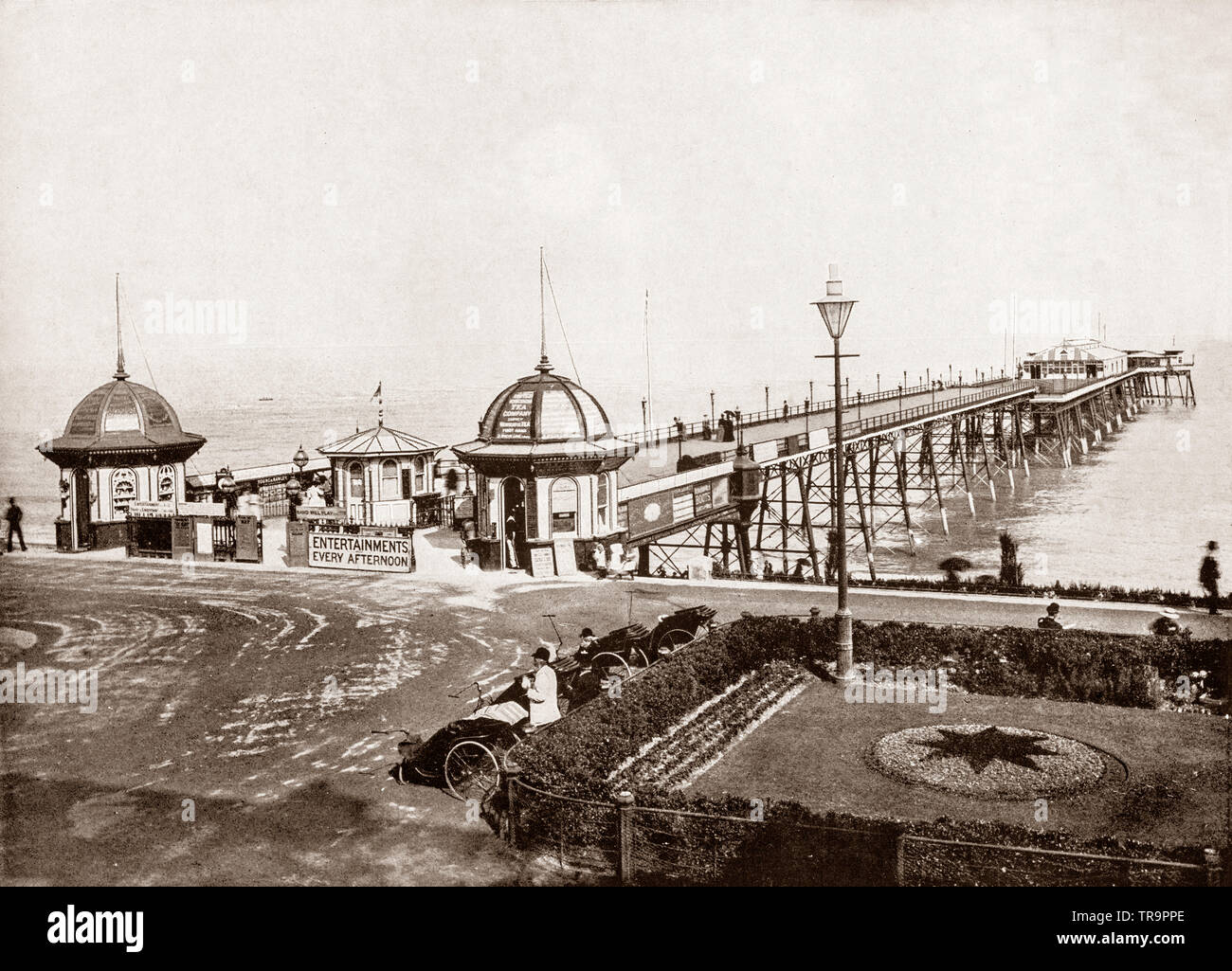 A 19th Century view of  Eastbourne Pleasure Pier in East Sussex, on the south coast of England. Roughly 300 metres (1000 ft) long, it was opened by Lord Edward Cavendish on 13 June 1870, although it was not actually completed until two years later. On New Year's Day 1877 the landward half was swept away in a storm. It was rebuilt at a higher level, creating a drop towards the end of the pier. The pier is effectively built on stilts that rest in cups on the sea-bed allowing the whole structure to move during rough weather. - Stock Image