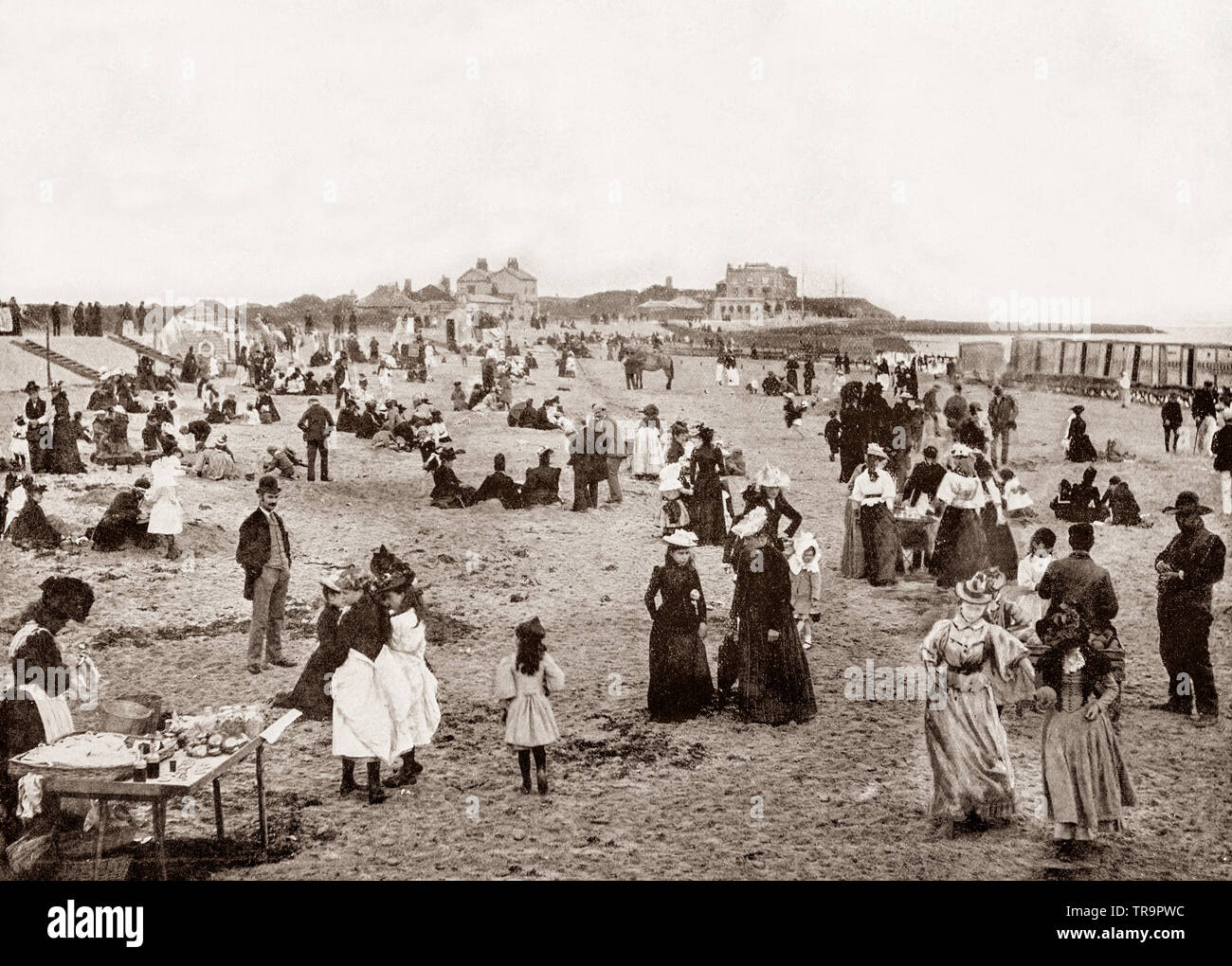 A 19th Century view of  holiday - makers on the beach at Walton-on-the-Naze, a small town in Essex, England, on the North Sea coast.  Originally, it was a farming village situated miles inland, but over the centuries a large extent of land has been lost to the sea due to coastal erosion. - Stock Image