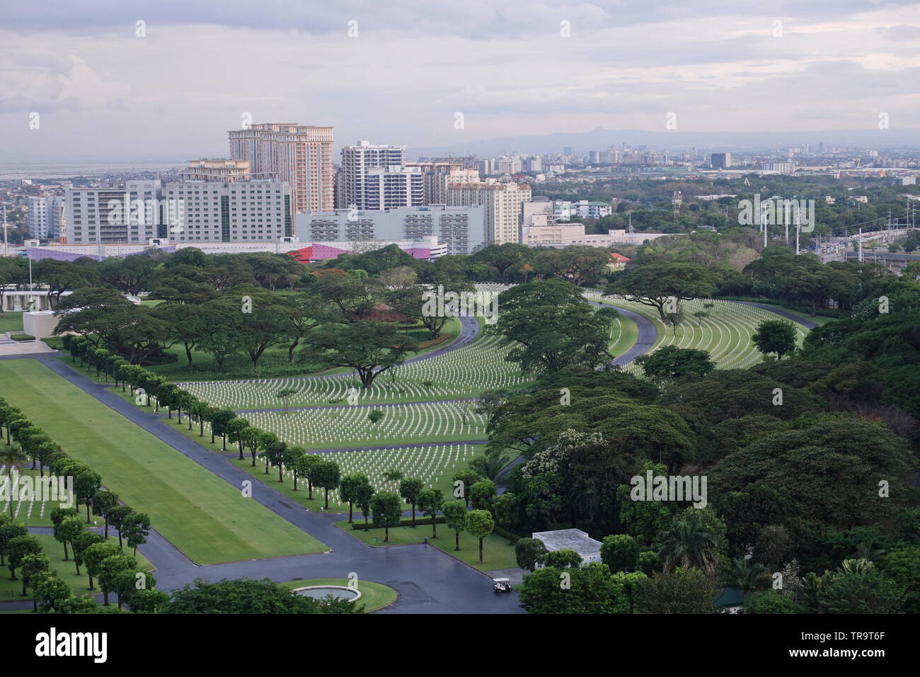 A view of the Manila America Cemetery and Memorial  and further off the city of Pasig across the river from a Bonifacio Global City condominium. - Stock Image