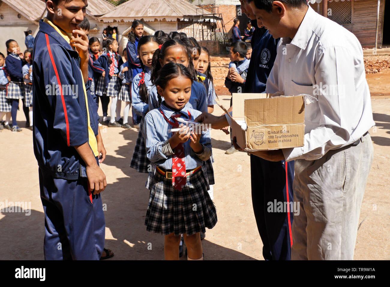 Children in school uniform accepting gift of new toothbrush from Global Grins charity, Samata Bamboo School, Bhaktapur, Kathmandu Valley, Nepal - Stock Image
