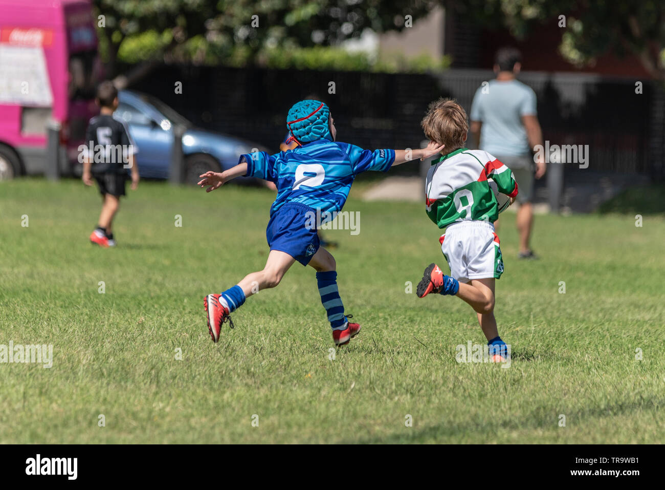 Australian football game kiss playing tackling each other - Stock Image