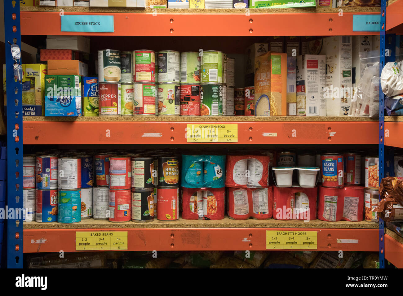 Tins of food stored on shelves at a food bank in Wembley, Greater London - Stock Image