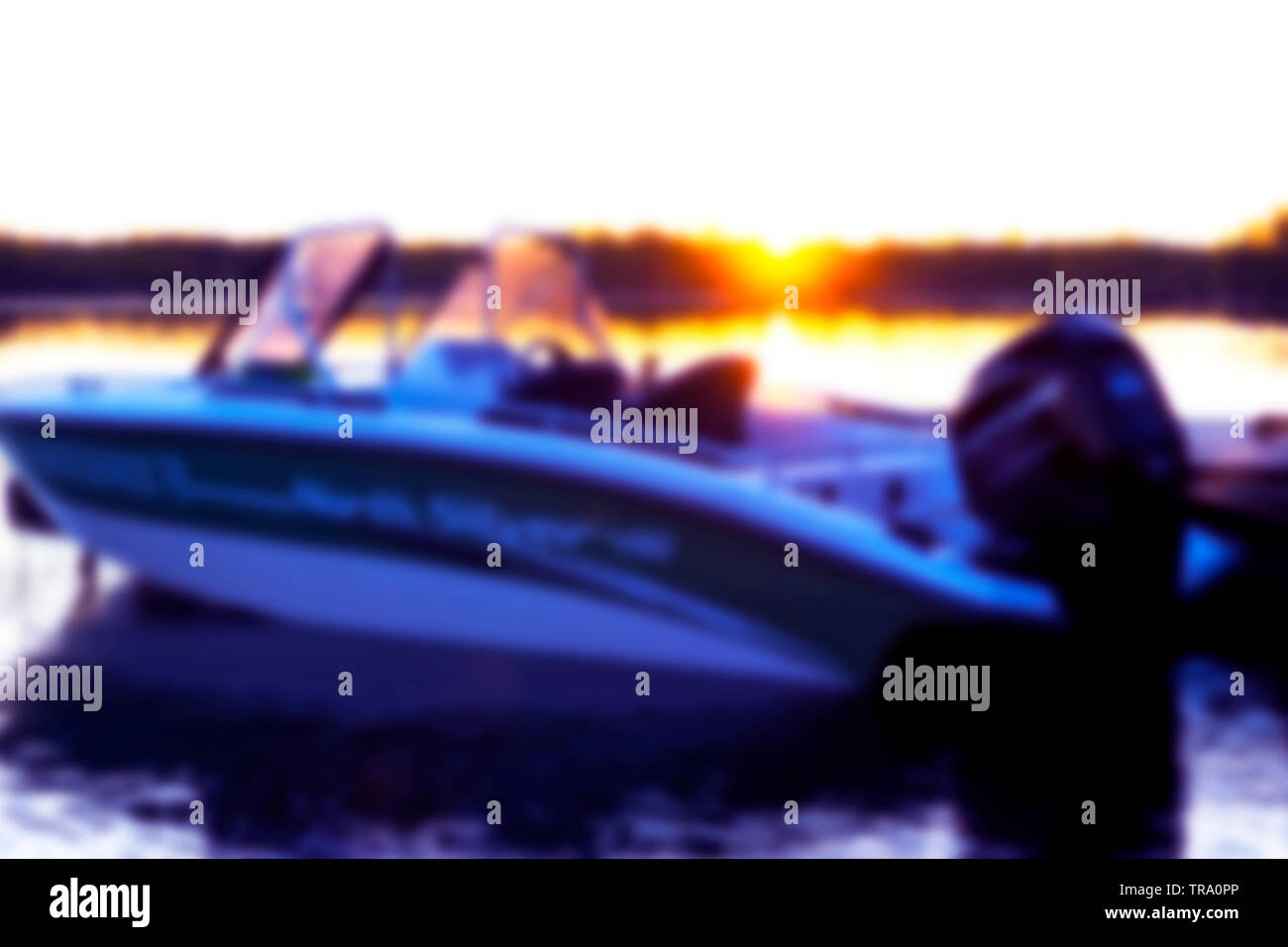 Abstract blurred background with fishing boat parking on the wooden pier. Sunset fishing boat blur background. Abstract blur background with bokeh lig - Stock Image