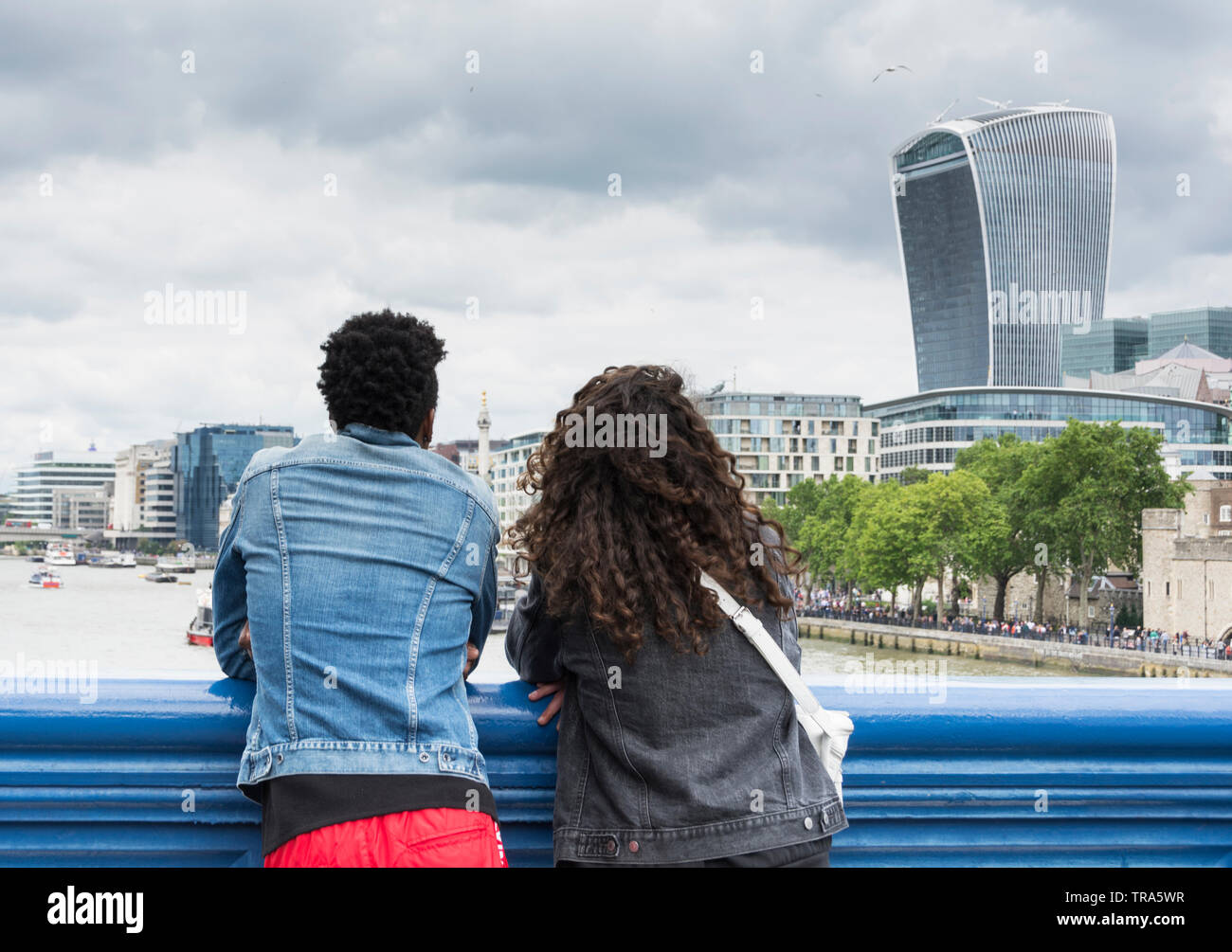 A young couple on Tower Bridge enjoying the view of the City of London's ever-changing skyline as new skyscrapers are added to the mix - Stock Image