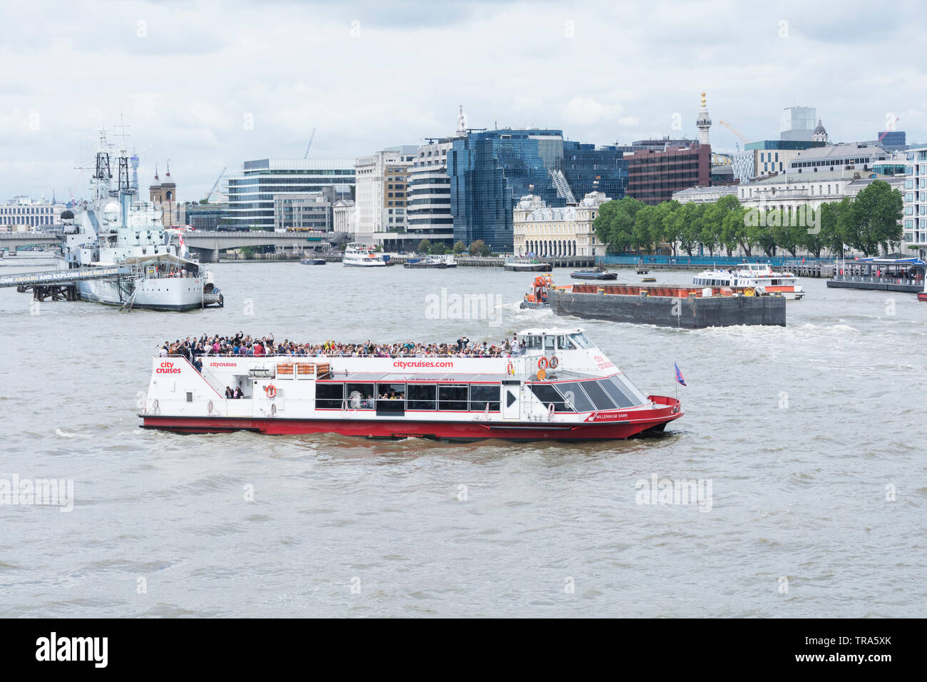 A City Cruises pleasure-boat in the Pool of London opposite the Tower of London with HMS Belfast in the background - Stock Image