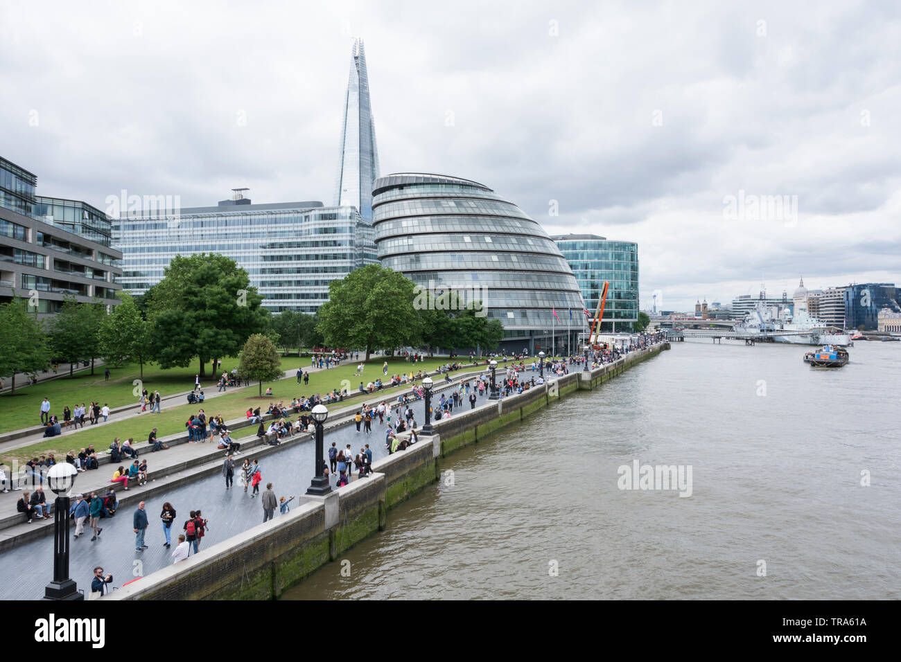 Tourists enjoying views of Norman Foster's London City Hall on the banks of the River Thames, London, UK - Stock Image