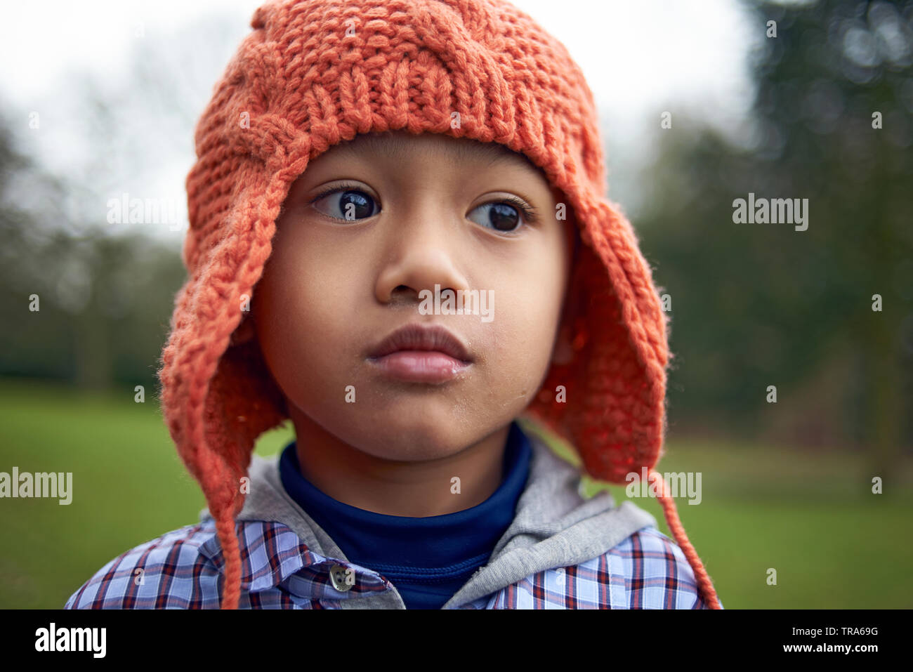 Adorable little Asian boy with big brown eyes wearing a wooley hat in a park in autumn - Stock Image