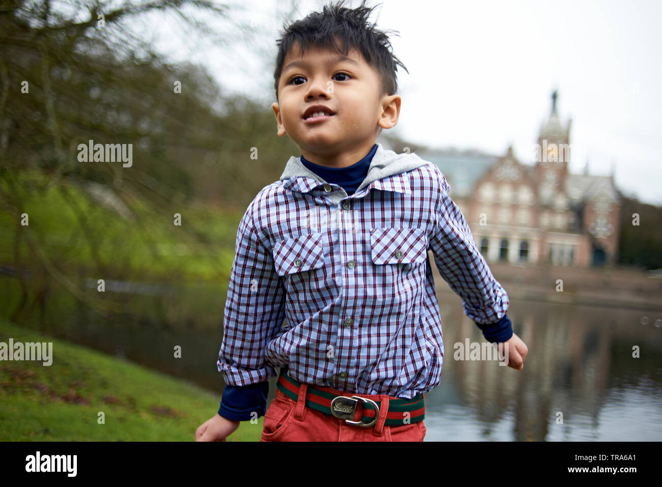 Adorable little Asian boy with big brown eyes in a park in autumn - Stock Image