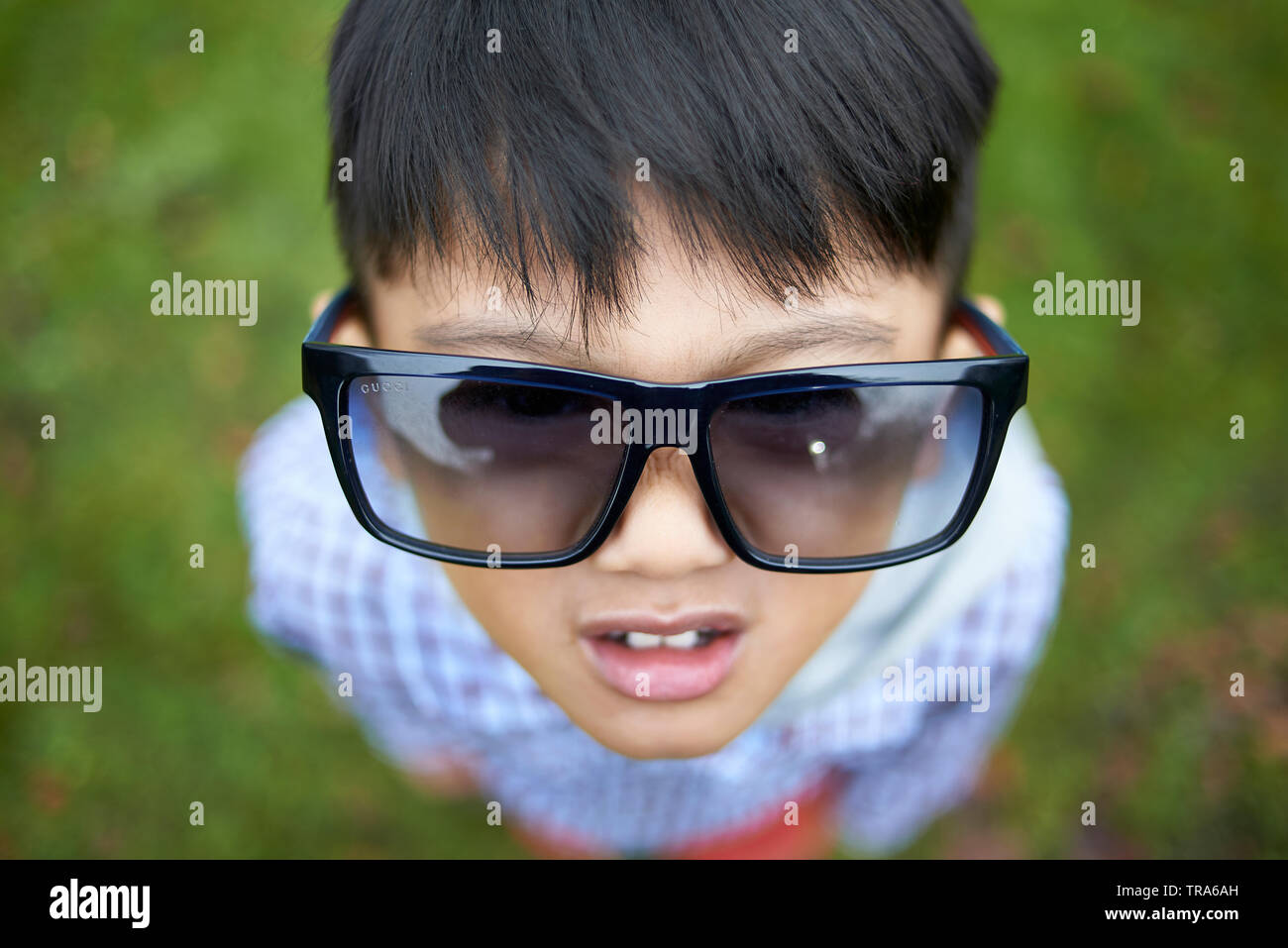 Portrait of an adorable little Asian boy with big brown eyes in a park in autumn wearing designer luxury sunglasses - Stock Image