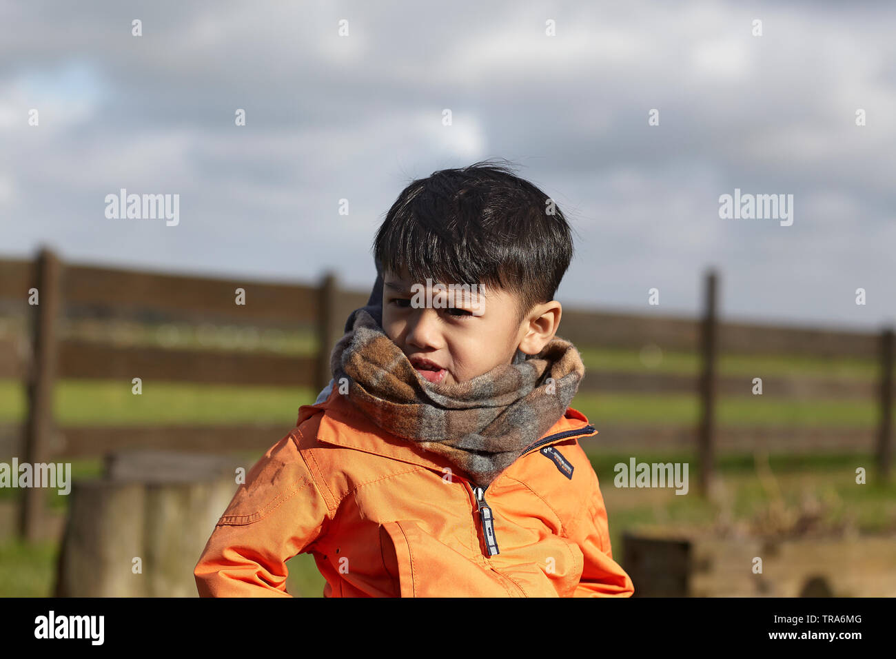 Portrait of an adorable little Asian boy with big brown eyeswearing winter clothing - Stock Image