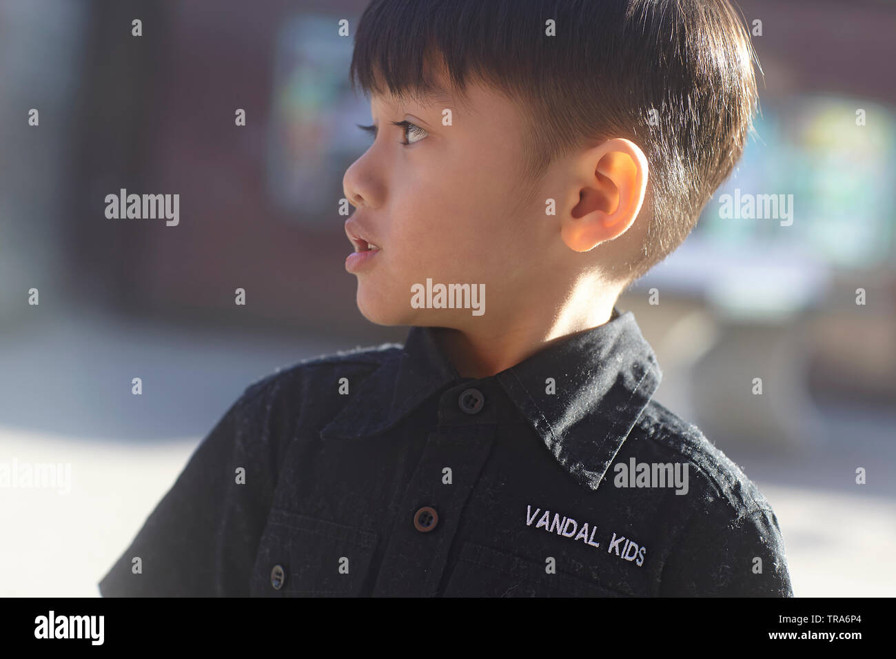 Adorable Asian boy standing on a fence in winter sunshine enjoying the playground - Stock Image
