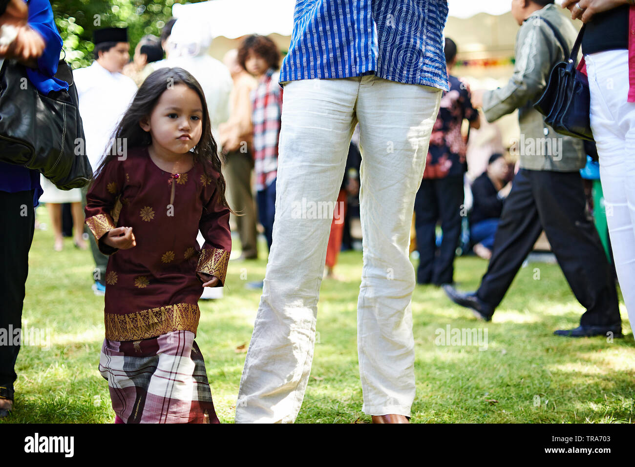 Two young Malay sisters wearing traditional Baju Kurung outfit during Hari Raya celebration happily running around between a crowd of people - Stock Image
