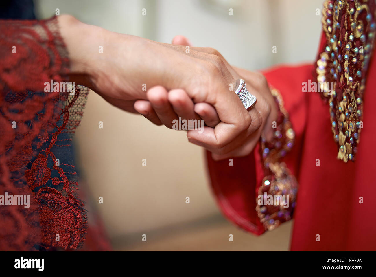 Close up of a mother holding her daughter's hand who is about to ask her for forgiveness, a tradition in Malay culture. Kissing of the hand - Stock Image