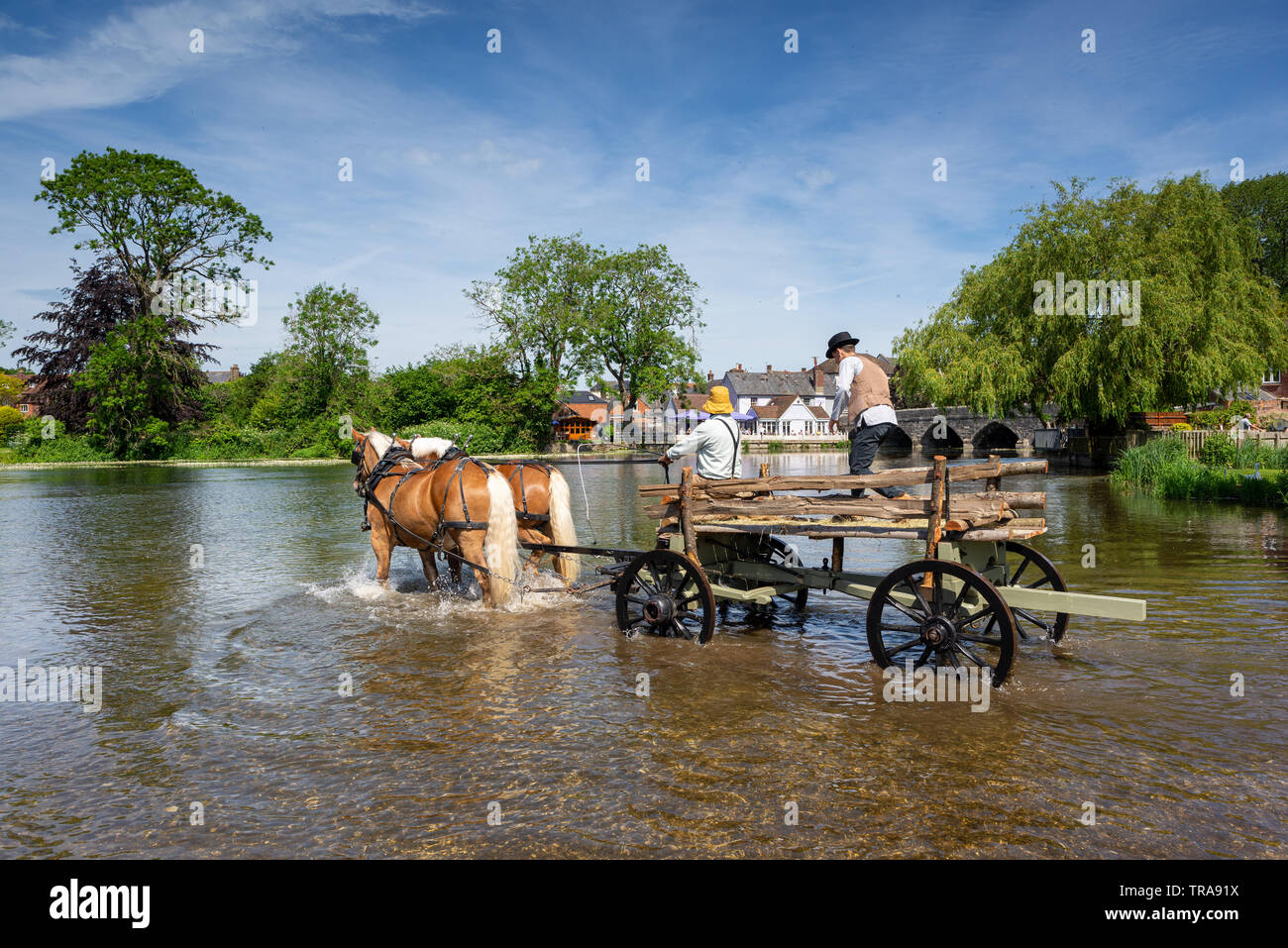 River Avon Fordingbridge, New Forest. Hampshire, UK, 1st June 2019. As part of culture week in the tow, local businessman Davide Shering deploys his Comtois heavy horses to create a scene similar to that in the Hay Wain, a painting by John Constable in 1821. Locals were invited to take part in a spot the difference competition with the original. Credit: Paul Biggins/Alamy Live News Stock Photo