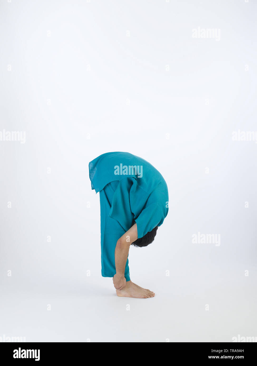 PORTRAIT OF A  YOUNG  BOY PERFORMING THE SURYA NAMASKAR POSE #3 CALLED Standing Forward Bend (Hasta Padasana) - Stock Image