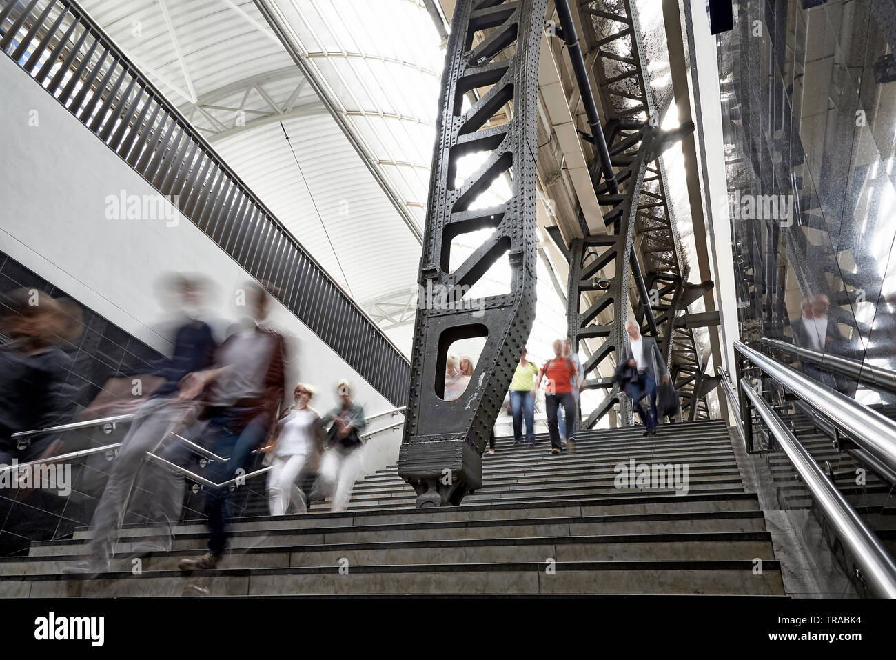Low angle of the stairs leading up to the platform at Amsterdam central station with crowds of people commuting - Stock Image