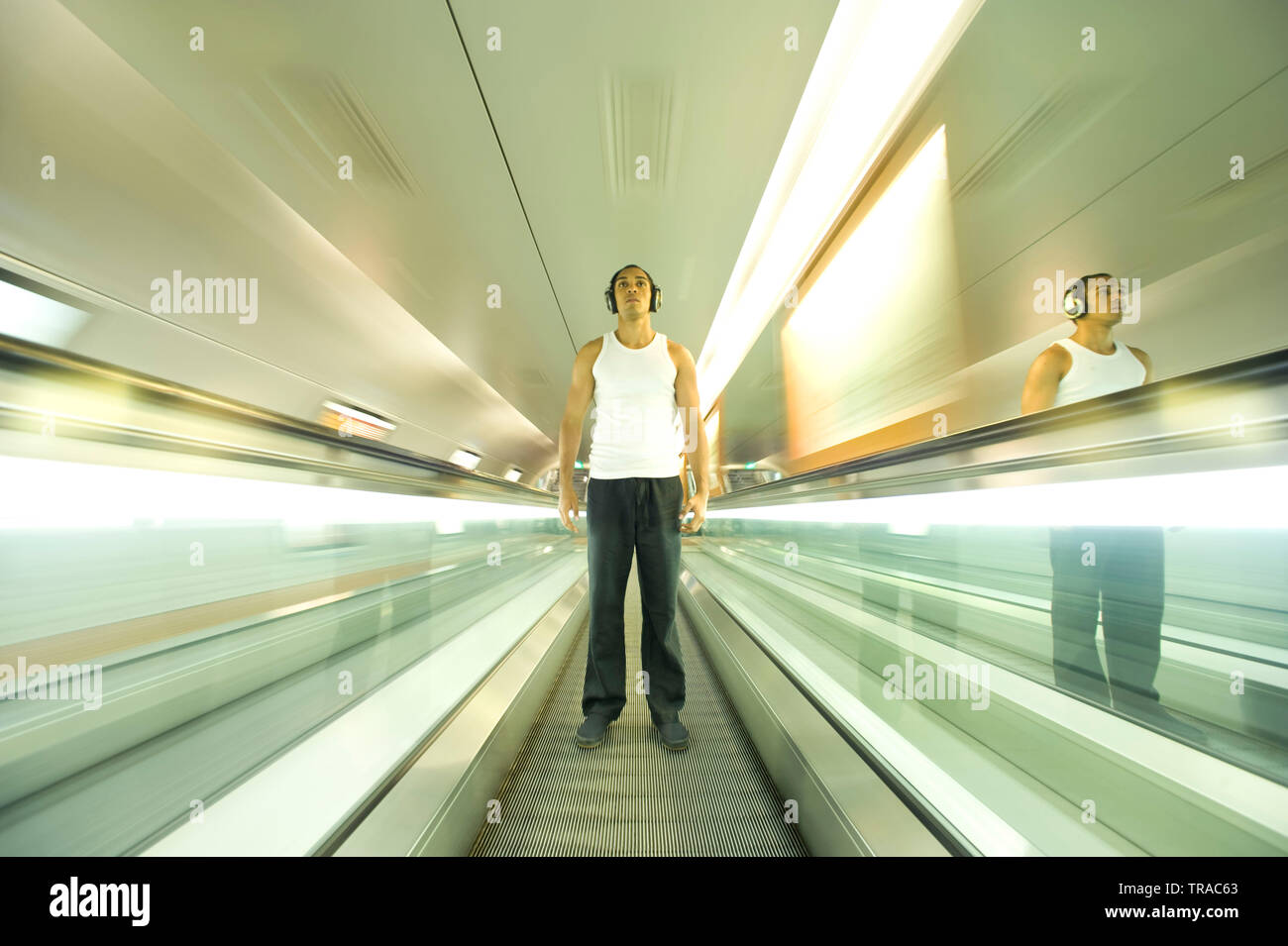 Amazing shot of a modern man standing on a moving escalator wearing headphones and listening to music - Stock Image