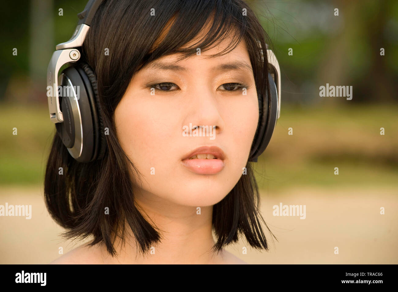 Portrait of a cool modern young Asian woman wearing big headphones listening to music - Stock Image