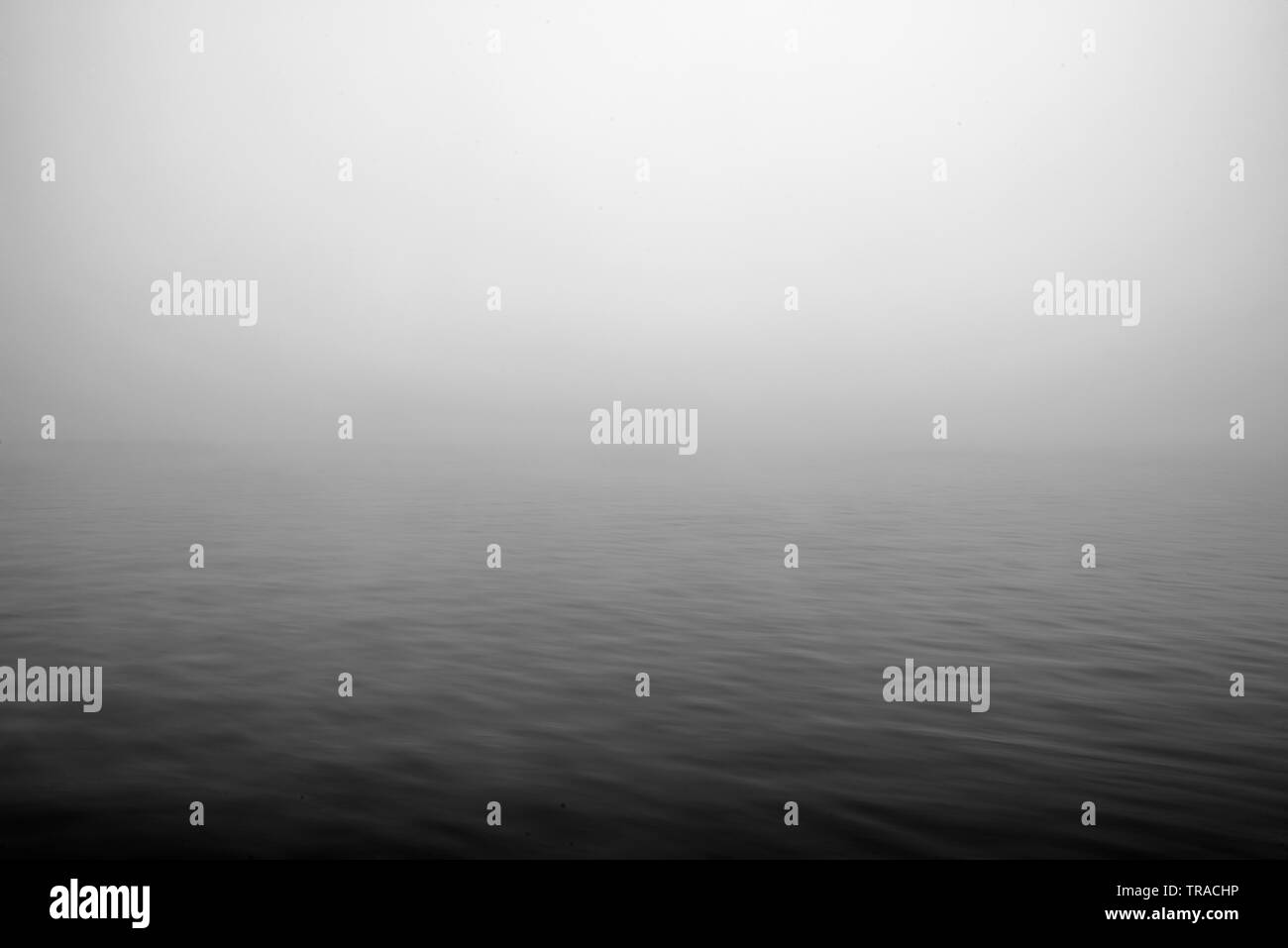 Stunning abstract shot of early moring fog hanging over the water of a lake giving it bad visibility - Stock Image