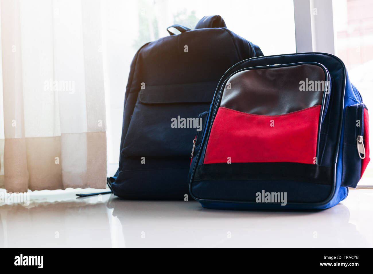 24b4904af0 Back to school concept. Blue backpack lean on the glass door for two ...