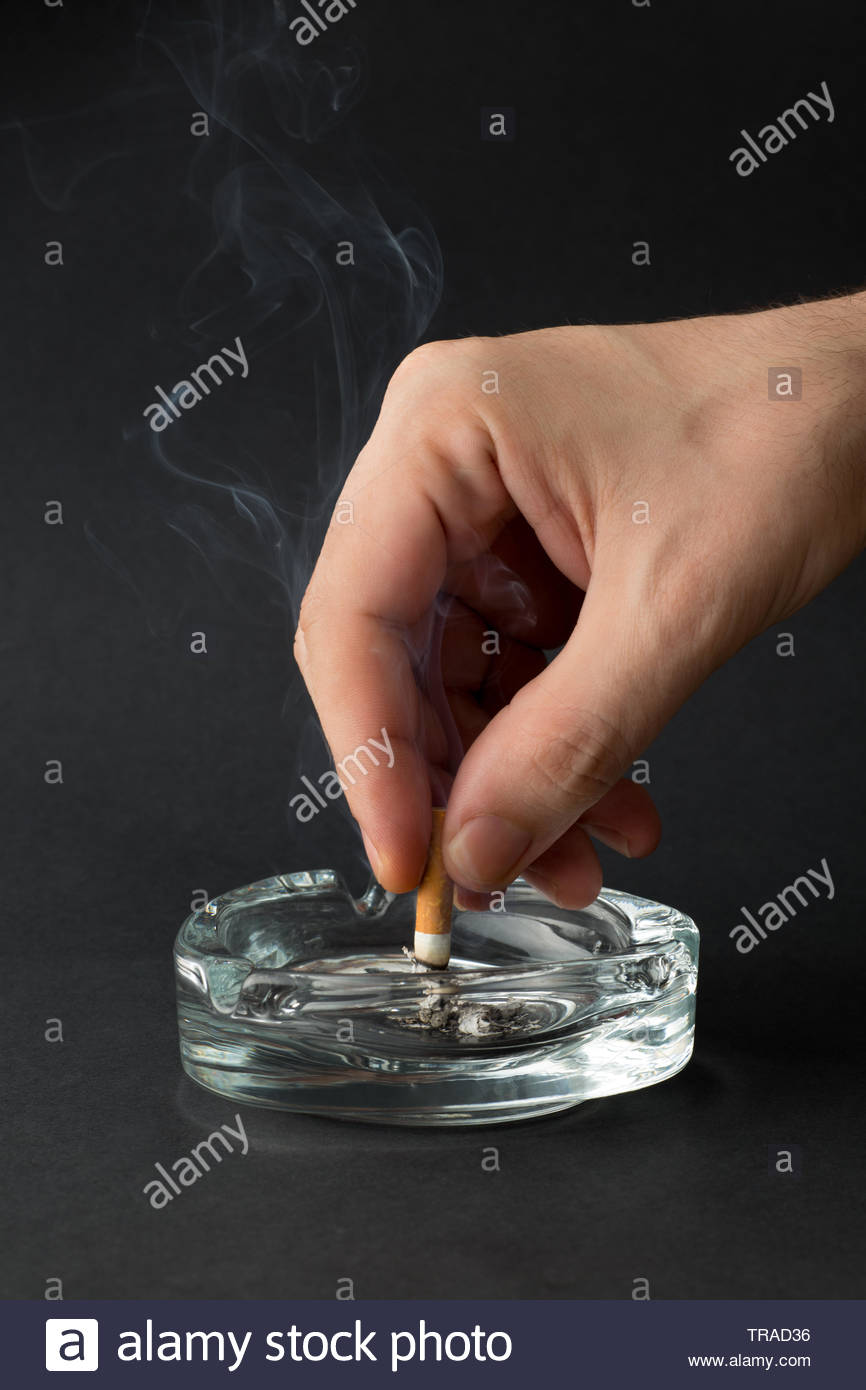 Cigarette with hand on black background - Stock Image