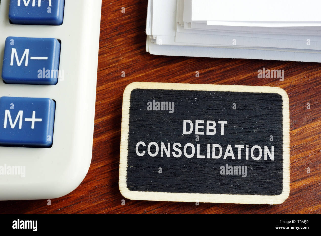 Debt consolidation loan. Nameplate with stack of documents. - Stock Image