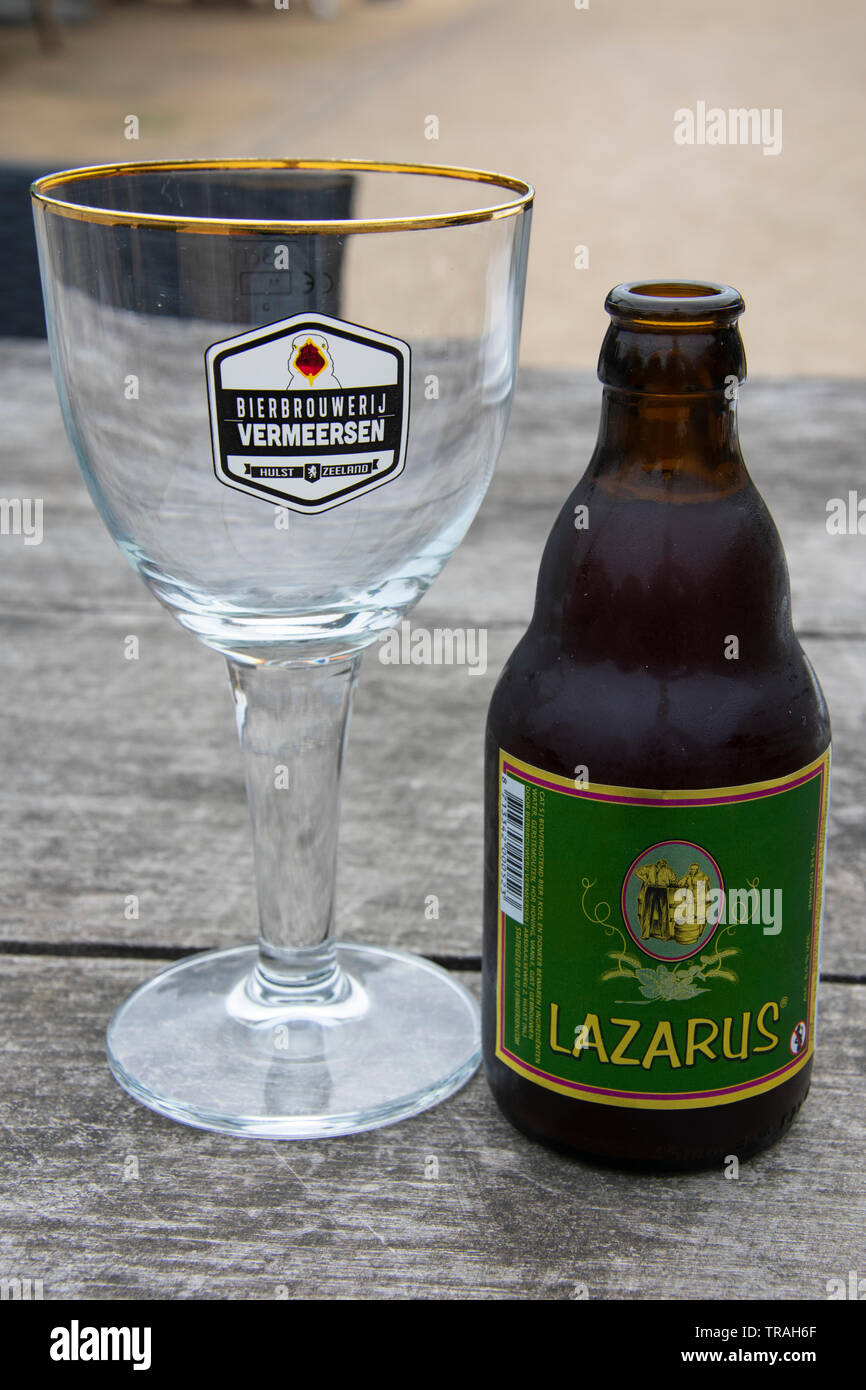 Hulst, Netherlands - july 19, 2018: Lazarus Netherlands beer on a garden terrace with empty glass of the brewery Vermeersen - Stock Image