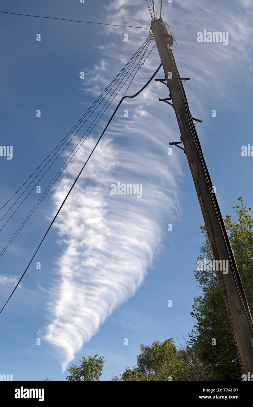 cirrostratus cloud seen against a blue sky behind a telegraph pole in twickenham, middlesex, england - Stock Image