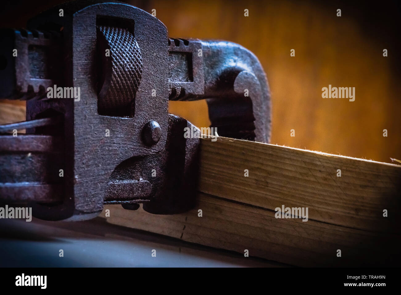 Rusted, stained pipe wrench hand tool clamped with a wooden block - Stock Image