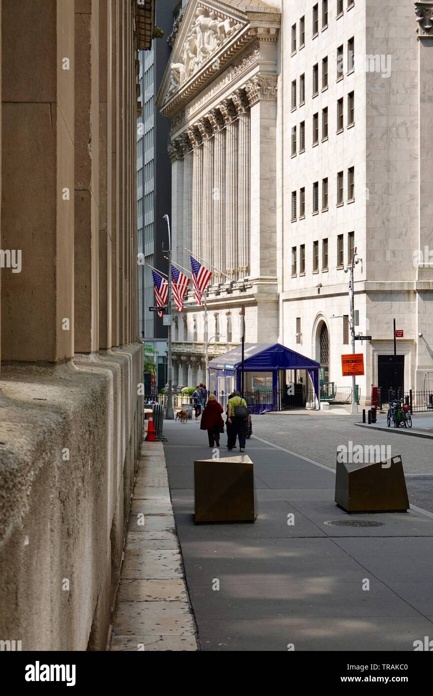 People walking towards the New York Stock Exchange building in the morning before the crowds of tourists, Manhattan, New York, NY, USA - Stock Image