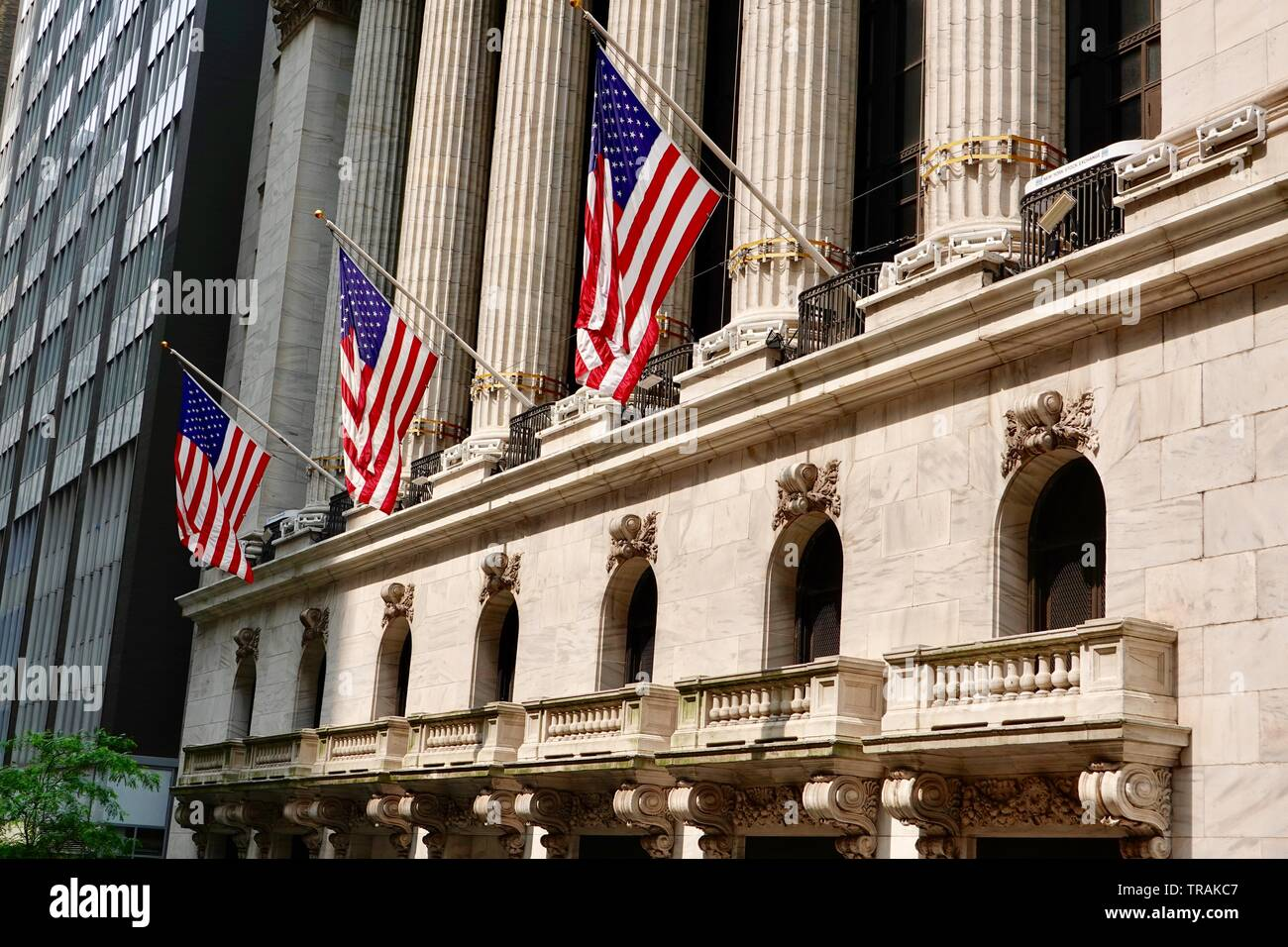 Three American flags fly in front of the New York Stock Exchange, Lower Manhattan, New York, NY, USA - Stock Image