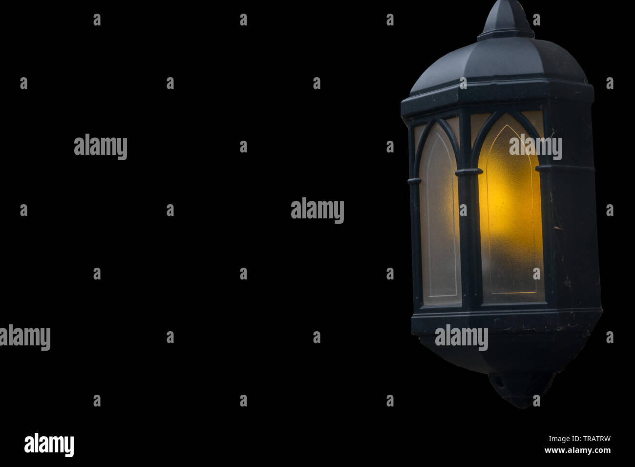 Lamps illuminate the evening attached to the house isolated over the black background. - Stock Image