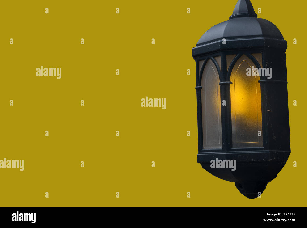 Lamps illuminate the evening attached to the house isolated over the yellow background. - Stock Image