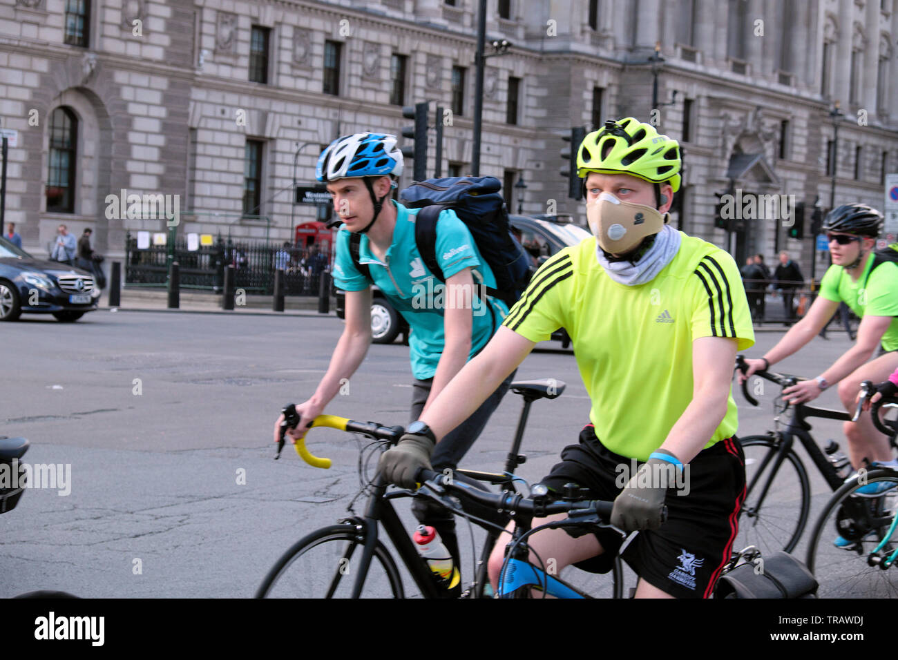 Cyclist wearing anti pollution mask to cut out toxic air particles cycling home after work rides bike by Houses of Parliament Westminster in London UK - Stock Image
