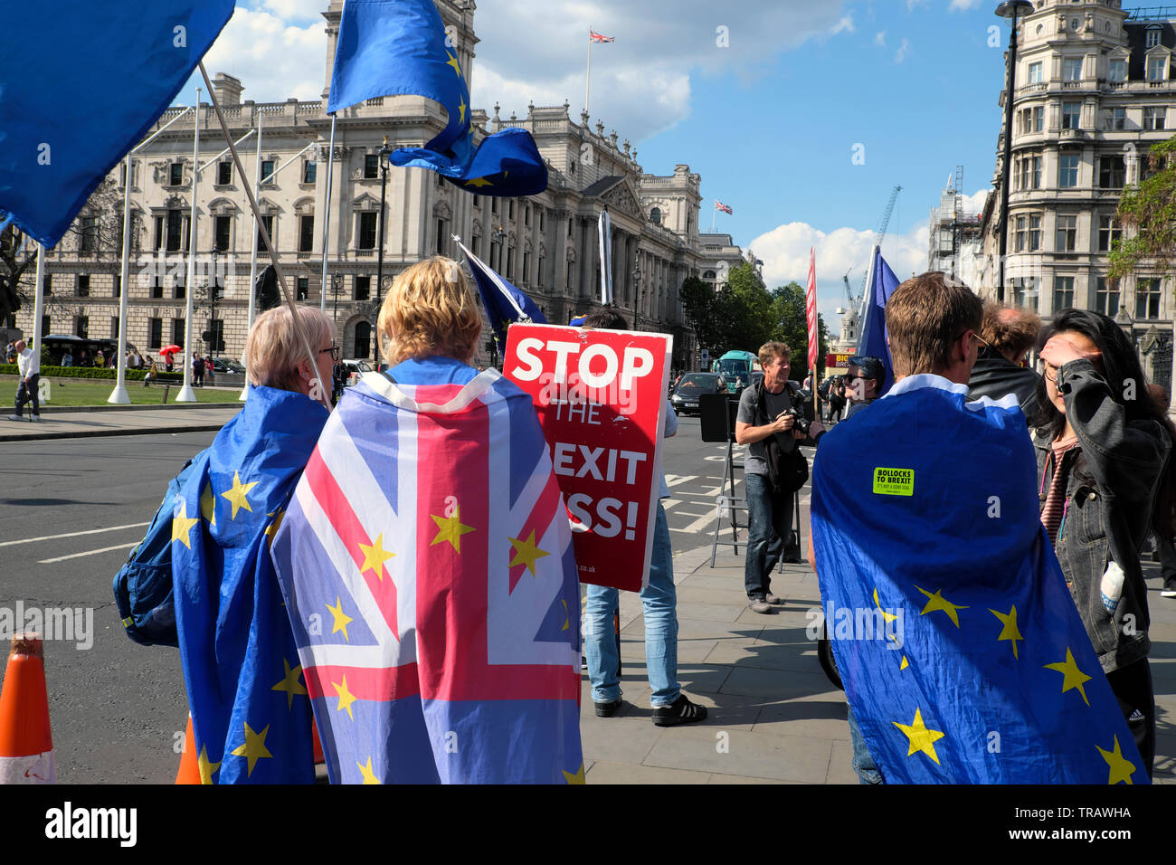 Rear view of protest in street outside the Houses of Parliament wearing Union Jack & European Union flags & Stop Brexit Mess London UK  KATHY DEWITT - Stock Image